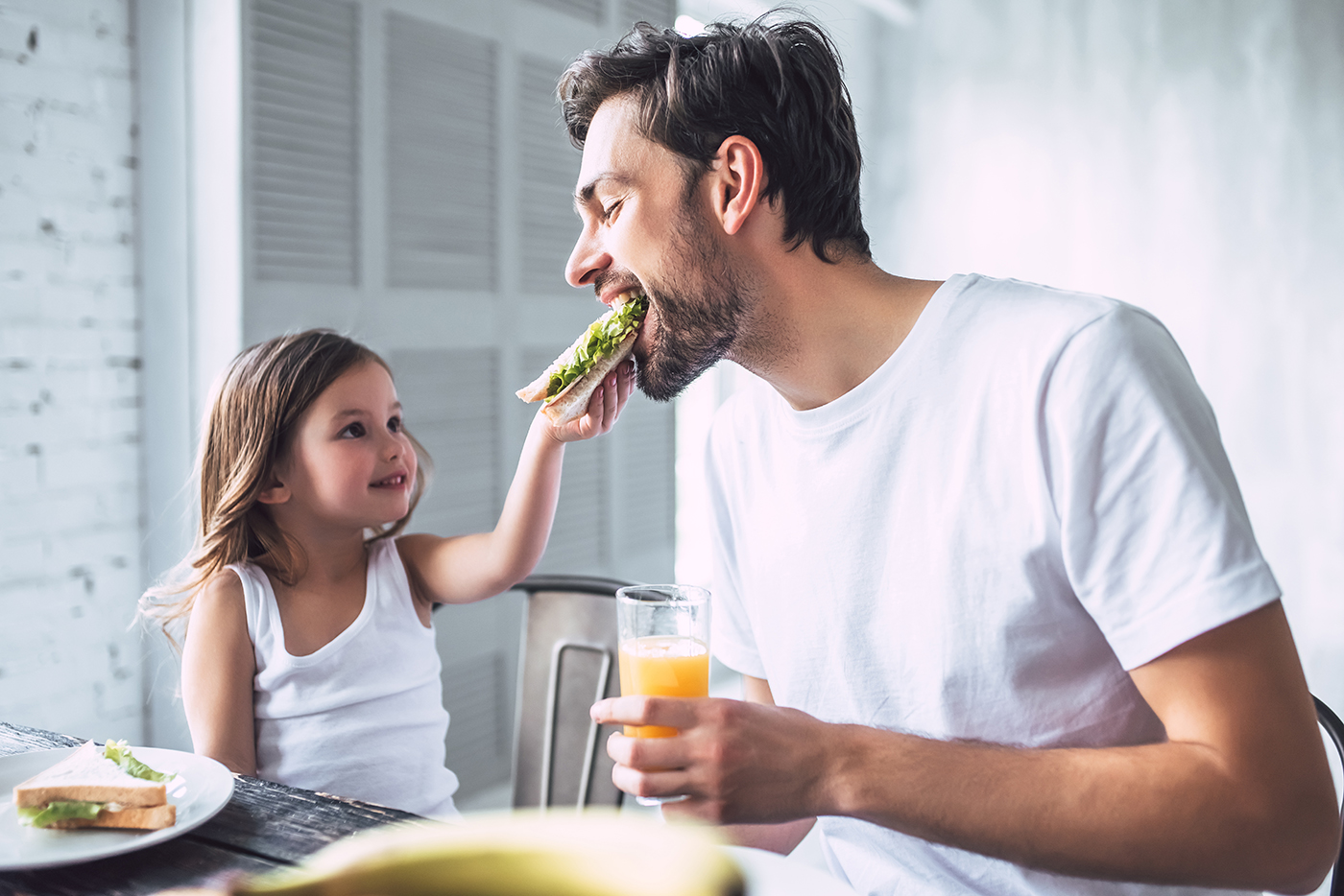 I love you, dad! Handsome young man at home with his little cute girl are having breakfast. Happy Father's Day!